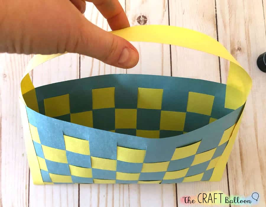 Paper Easter basket craft with handle attached.