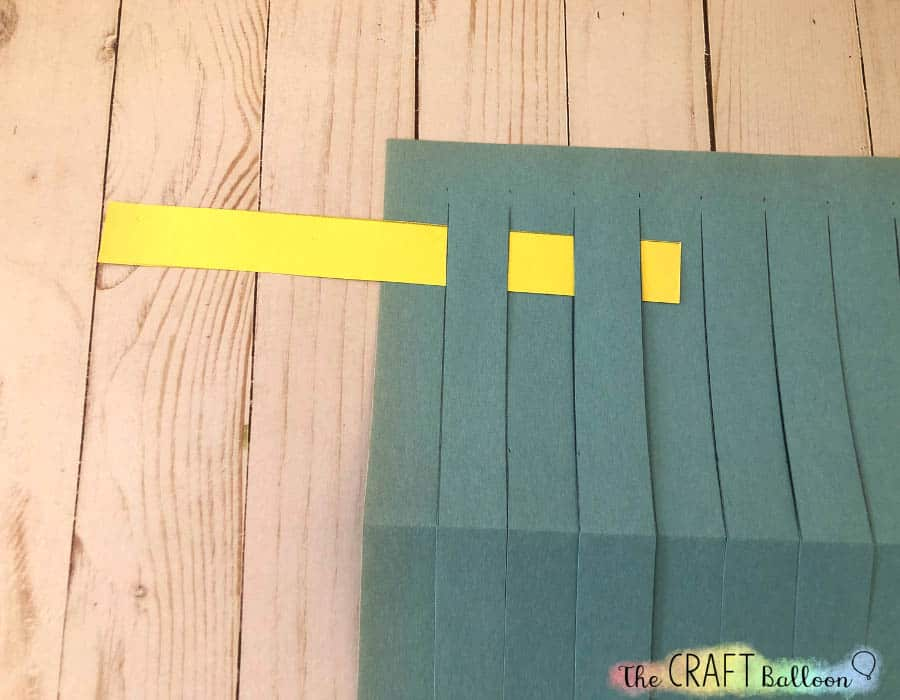 First paper strip being woven through blue paper